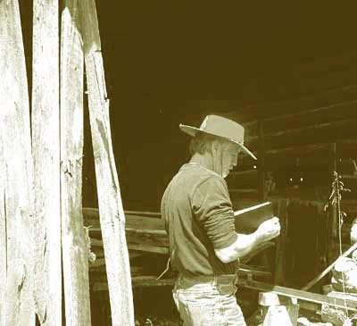 Photo of Daniel Ambrose writing in journal in a barn